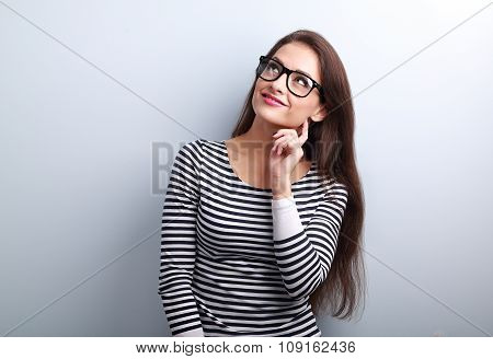 Pretty Casual Thinking Woman In Glasses Looking Up On Blue Background