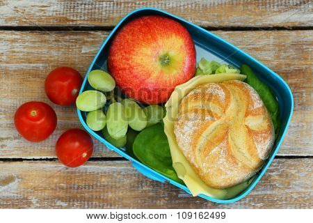 School lunch box consisting cheese roll, red apple, grapes and cherry tomatoes