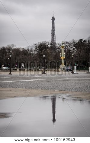 The Eiffel Tower and his reflection in a puddle as seen from the Concorde Square in Paris, France. Winter season.