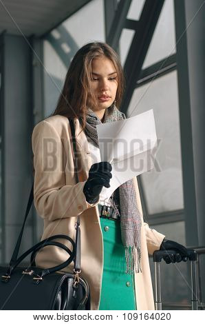 Woman Reading Letter And Holding Suitcase