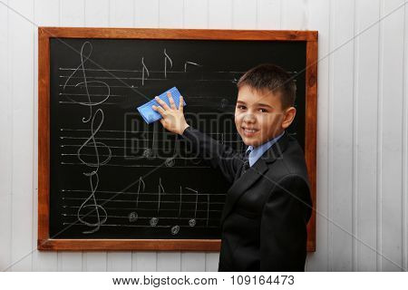 Young cute schoolboy cleaning the blackboard with musical notes