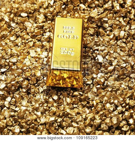 Gold bar and nugget grains, on grey background