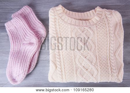 Hand made warm clothes on wooden background