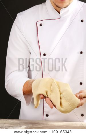 Man preparing dough basis for pizza on the wooden table, close-up
