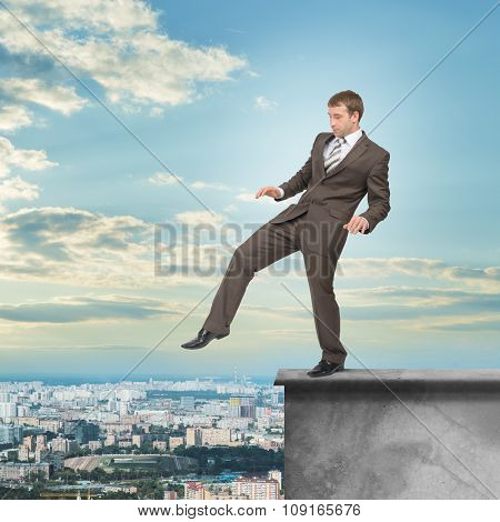 Businessman stepping from edge of building roof