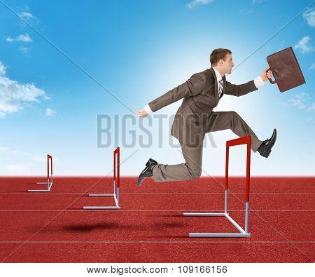 Businessman hopping over treadmill barrier