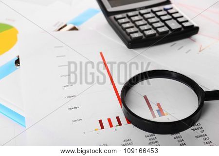 A magnifying glass on financial documents background, close-up