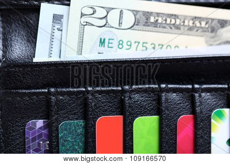Black leather wallet with colourful credit cards and money, close up