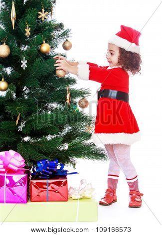 girl decorates the Christmas tree