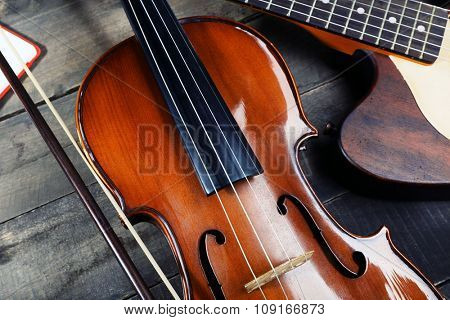Electric guitar and violin on wooden background