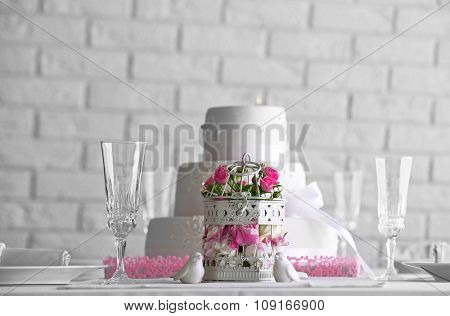 Layered wedding cake and flowers in cage on decorated table