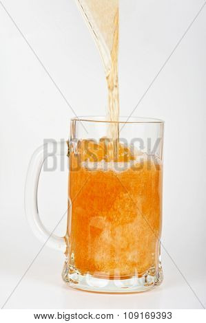 beer is pouring into glass on white background
