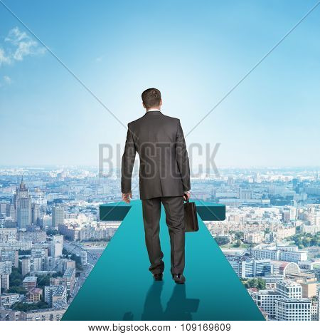 Businessman on blue arrow above city