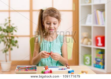 Kid playing modeling plasticine or molding clay