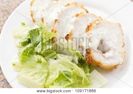 Sliced chicken cordon bleu with creamy sauce and romane leaf salad