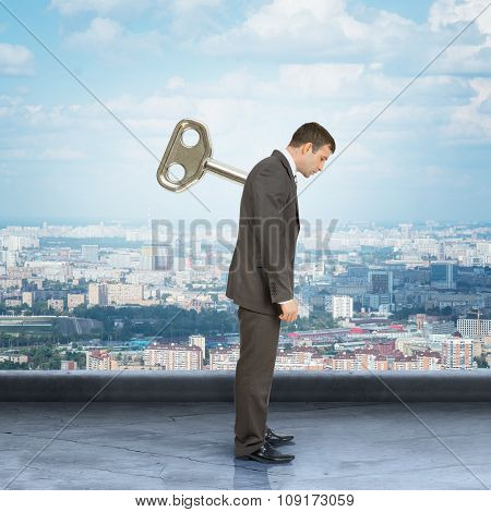 Man with key in back and city