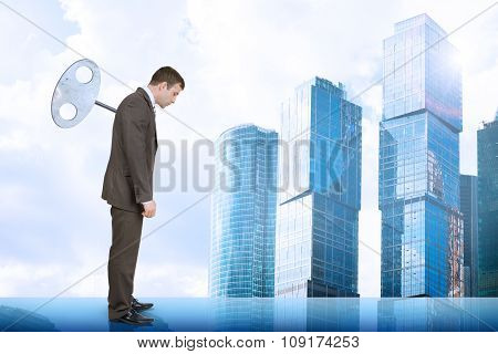 Businessman with key in back and city scape