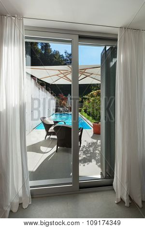 Interior of a modern house, window with access to the pool