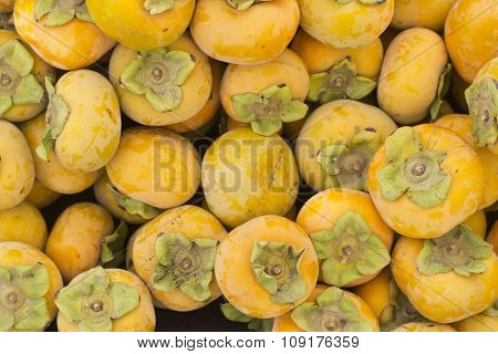 Organic persimmon fruits in pile at local farmers market