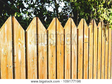 Wooden Fence With Green Lawn And Houses.