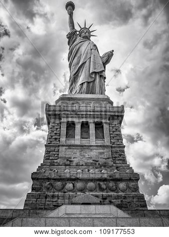 Black and white image of the Statue of Liberty in New York City with a dramatic cloudy sky