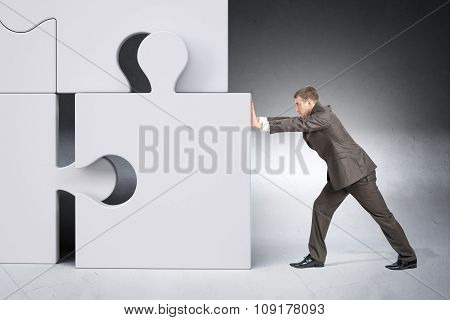 Man in suit pushing grey puzzle piece