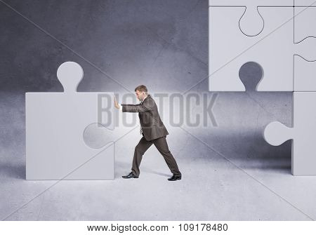 Businessman in suit pushing grey puzzle piece
