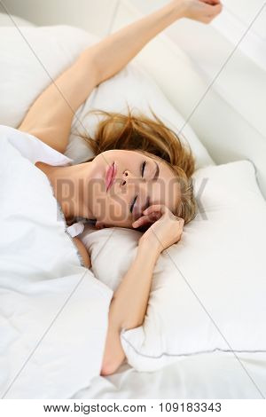 Young Beautiful Blonde Woman Lying In Bed Trying To Wake Up