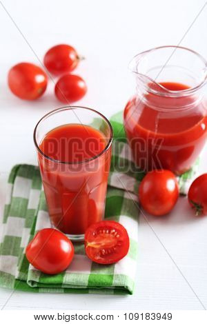 Fresh Red Tomatoes In Basket And Tomato Juice In Glass And Jug On White Wooden Table