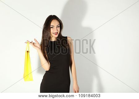 Young Brunette Woman In Black Dress With Shopping Bags On A White Background