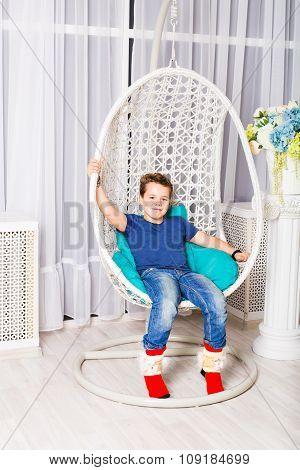 little boy sitting on white chair