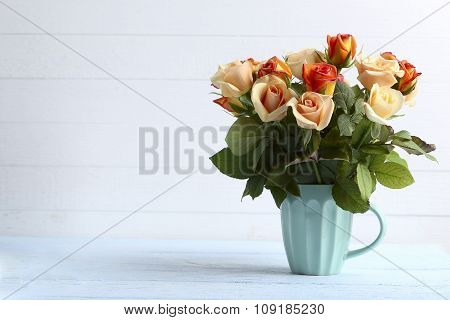 Bouquet Of Orange Roses In Cup On Blue Wooden Background