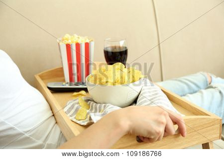 A girl with a tray having lunch on a sofa, close-up