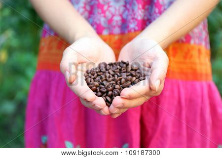 Woman holds in hands roasted coffee beans