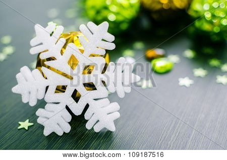 White Snowflake On Background Of Gold And Green Xmas Baubles.