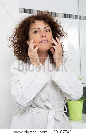 Portrait Of A Lady With A Bathrobe On Looking At Her Skin's Face In The Mirror