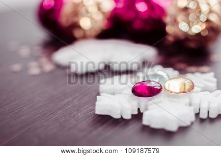 White Snowflakes On Background Of Magenta And Gold Xmas Baubles.