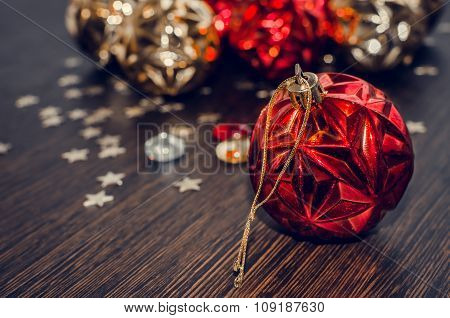 Red Christmas Ball On Bokeh Background Of Xmas Ornaments.