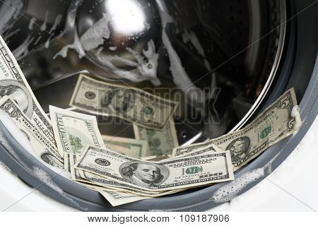 Laundered money in washing machine, close up