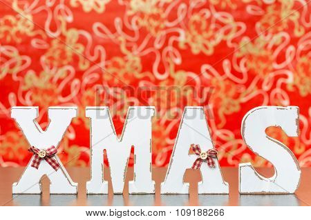 Wooden Letters Forming Word Xmas With Ribbons And Buttons, With Red Background