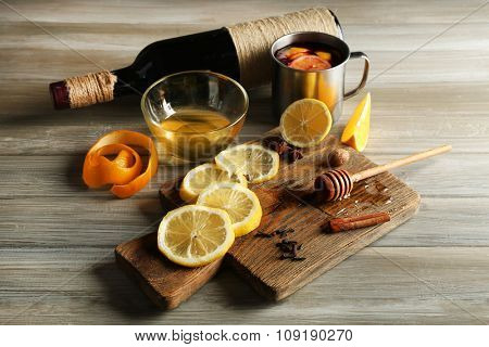 Delicious mulled wine in a mug with citruses on decorated wooden background