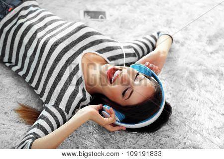 Woman listening music in headphones on carpet in room