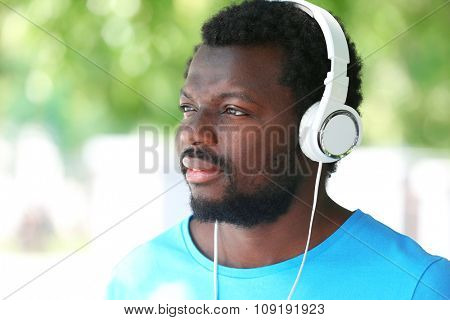 African American man listening music with headphones on blurred background