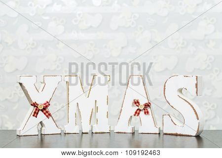 White Wooden Letters On Brown Wooden Table Forming Word Xmas With Ribbons And Buttons