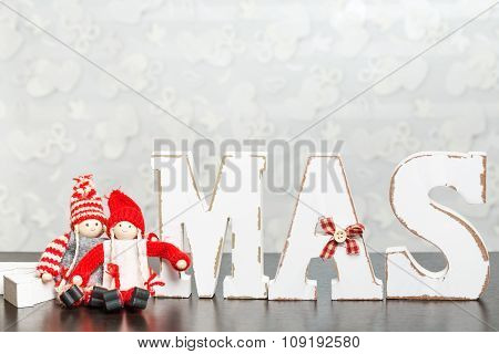 White wooden letters on brown wooden table forming word XMAS with ribbons and a couple represented b