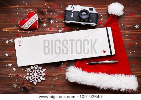 Christmas And New Year Background With Old Camera, Santa's Hat, Notepad With Pen