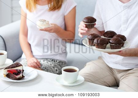 Friends hands with cups of tea and desserts, close up