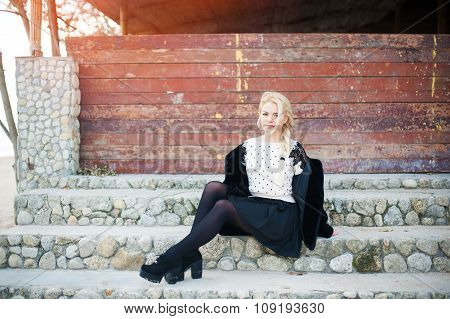 Beautiful blonde  woman wearing fashionable clothes sitting on stairs