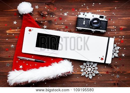 Christmas And New Year Background With Old Camera, Santa's Hat, Notepad and Photo
