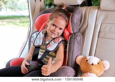 Adorable little girl in the car with teddy bear